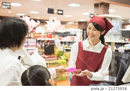 スーパーのレジで買物する親子の...